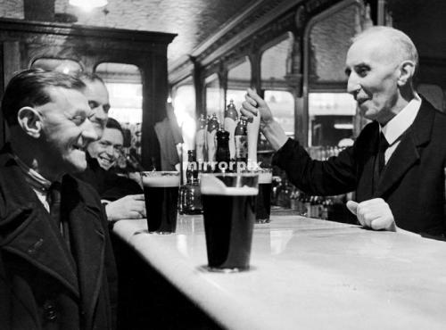 Landlord James Downeyserving a pint to one of his regulars. 16th February 1948