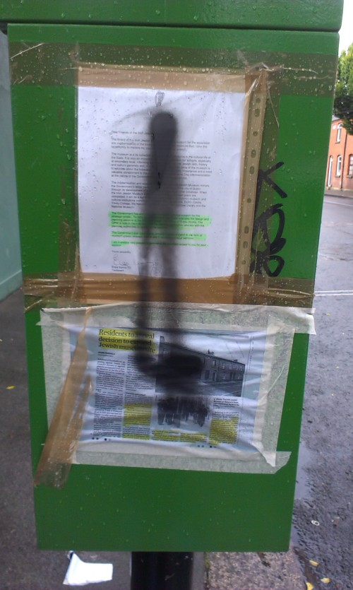 An individual has used black spray paint to cover newspaper articles which critised the plan