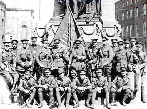 Members of the British forces pose with the captured 'Irish Republic' flag at the Parnell statue, opposite Thomas Clarke's shop.