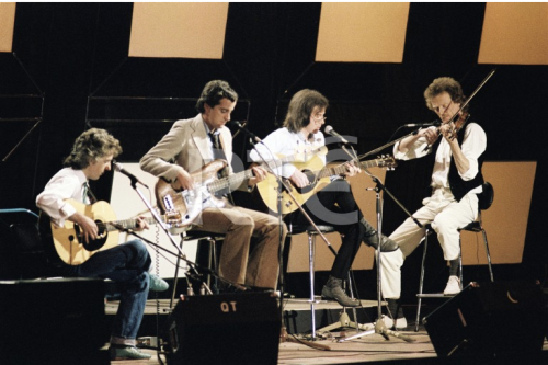 Hotfoot on stage at the National Stadium in September 1983. From left to right; Jimmy Faulkner on acoustic guitar, Declan McNelis on bass guitar, Jimmy Gibson on acoustic guitar and violinist Pat Collins. This concert was recorded and televised as part of RTÉ Television's 'Festival Folk' series on 14 March 1984. Credit - stillslibrary.rte.ie