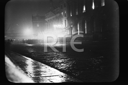 """A night shot of people gathered outside the Tivoli Theatre on Dublin's Burgh Quay, circa 1920. The White Horse Inn can be seen in the background. Credit - RTE"